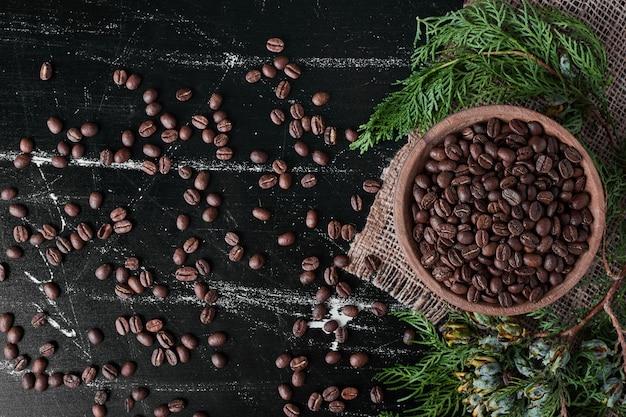 Koffiebonen op zwarte achtergrond in de houten kop. Gratis Foto