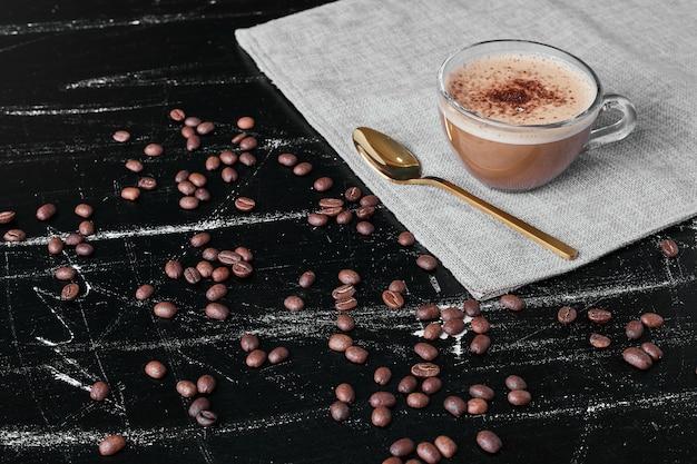 Koffiebonen op zwarte achtergrond met drank. Gratis Foto