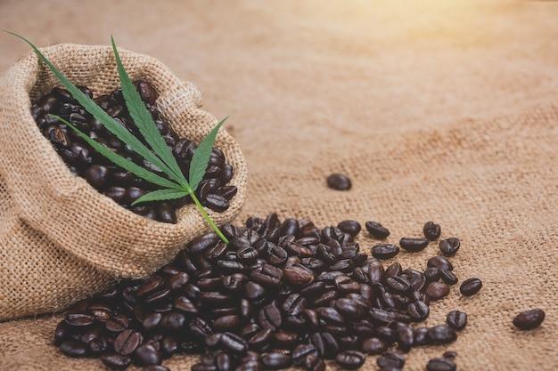 Koffiebonen worden uit de zak op de vloer van de zak gegoten en een henneptop wordt gelegd Gratis Foto