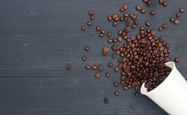 Koffieboon in witte hete kop op zwarte houten achtergrond Premium Foto