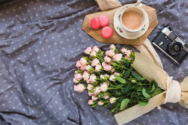 Koffiekop; bitterkoekjes; camera en bloemboeket op tafelkleed Gratis Foto