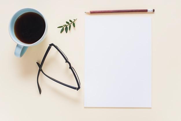 Koffiekop; bril; takje; potlood en lege witte pagina op beige achtergrond Gratis Foto