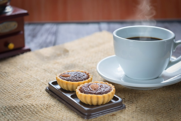 Koffiekop en koffiebonen met brownietaartjes Premium Foto