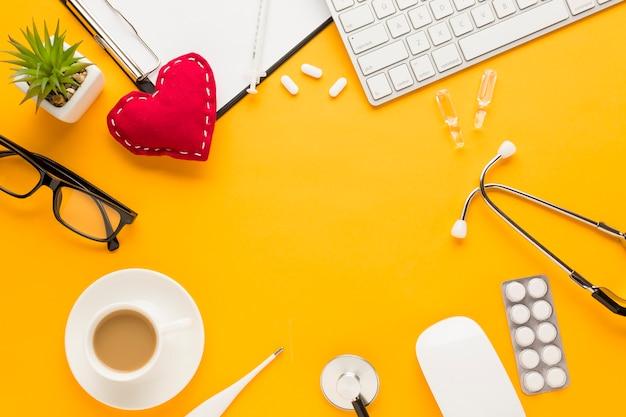 Koffiekop; met blister verpakt medicijn; toetsenbord; lenzenvloeistof; vetplant; thermometer; injectie; gestikte hartvorm; stethoscoop; klembord over gele achtergrond Gratis Foto
