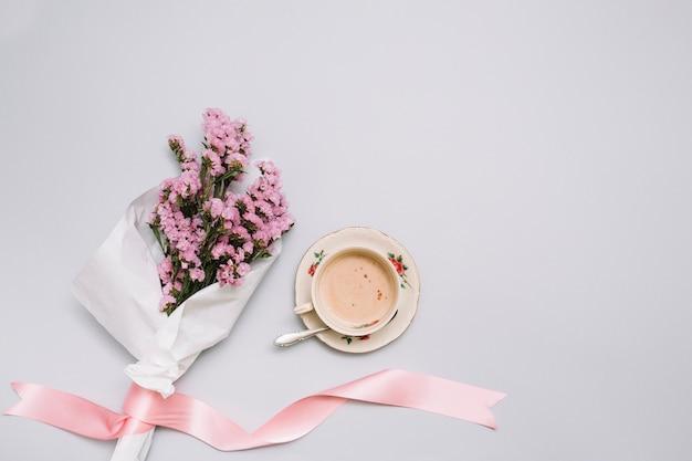 Koffiekop met bloemenboeket op lijst Gratis Foto