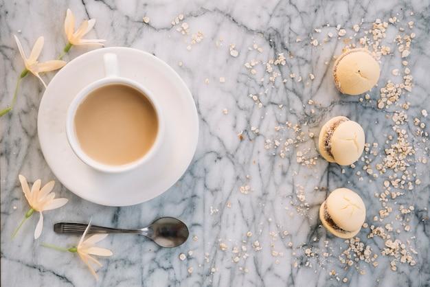 Koffiekop met koekjes en bloemen op tafel Gratis Foto