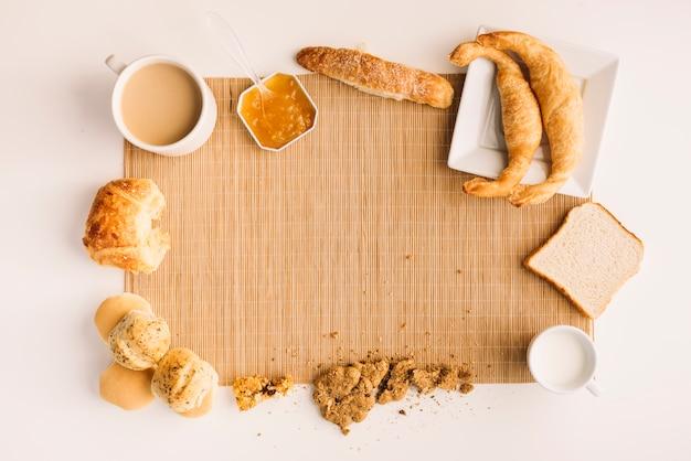 Koffiekop met verschillende bakkerij en jam op tafel Gratis Foto