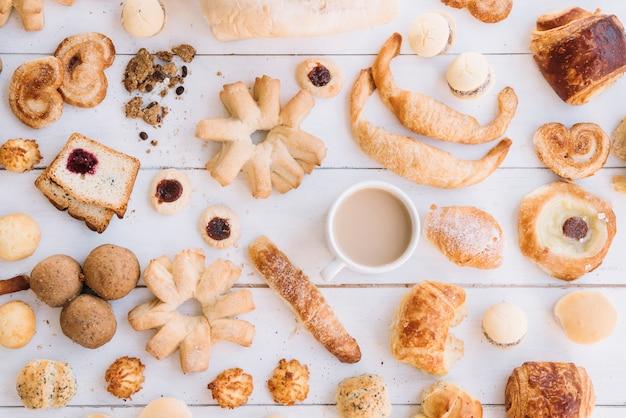 Koffiekop met verschillende bakkerij op houten lijst Gratis Foto