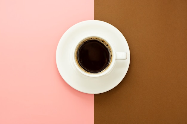 Koffiekop op bruine en roze lijst wordt geïsoleerd die. plat lag abstracte zwarte koffie Premium Foto