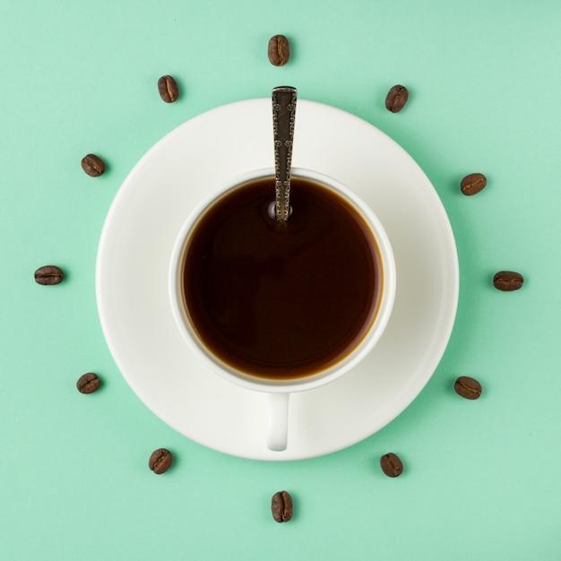 Koffiekopje en geroosterde bonen gerangschikt als wijzerplaat, bovenaanzicht. koffietijd. interessant idee energie en verfrissing concept. Premium Foto