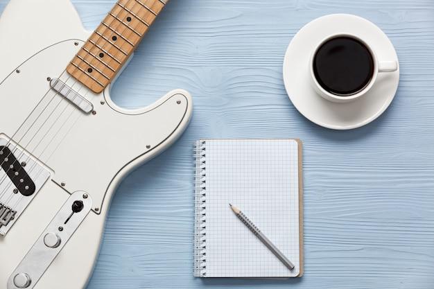 Koffiekopje en gitaar op houten tafel met notebook en potlood Premium Foto