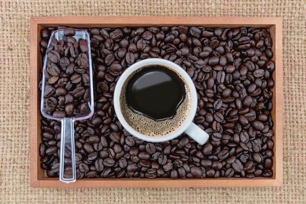 Koffiekopje en koffiebonen in doos Premium Foto