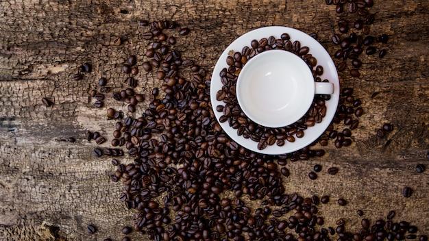 Koffiekopje en koffiebonen op houten tafel. donkere tafel. Premium Foto