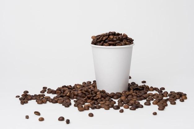 Koffiekopje gevuld met koffiebonen Gratis Foto