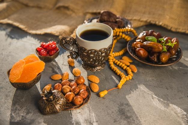 Koffiekopje met dadelsfruit en verschillende noten Gratis Foto