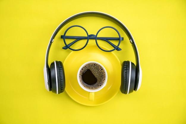 Koffiekopje met hoofdtelefoon en leraar bril op geel papier achtergrond Premium Foto