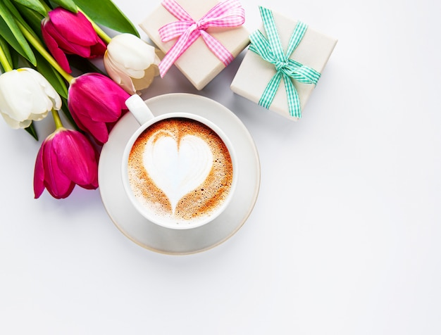 Koffiekopje met latte kunst en tulpen Premium Foto