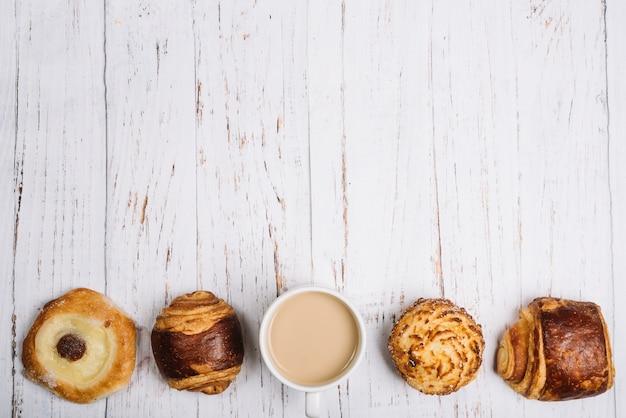 Koffiekopje met zoete broodjes op tafel Gratis Foto