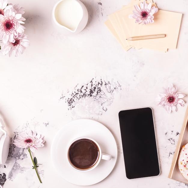 Koffiekopje op een schoteltje en een smartphone Premium Foto