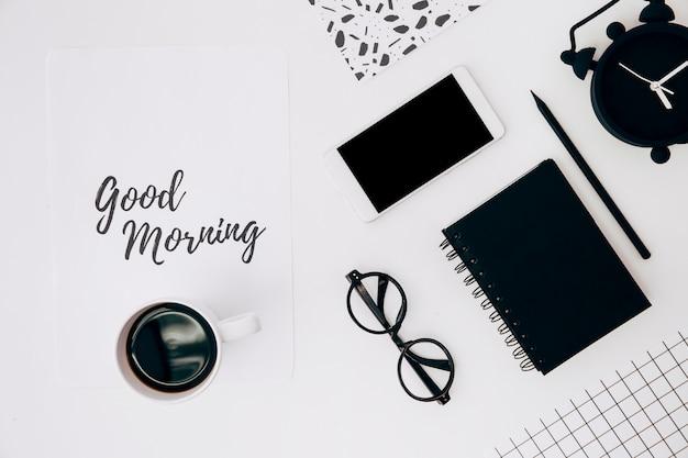 Koffiekopje over papier met goedemorgenstekst; mobiele telefoon; wekker en kantoorbehoeften op wit bureau Gratis Foto