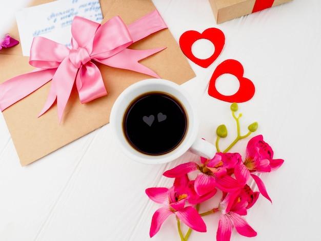 Koffiekopje, sluit roze geschenken, letters en twee harten in de beker. Premium Foto