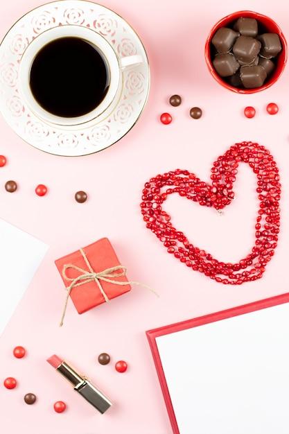 Koffiekopje, snoepjes, lippenstift, hartvorm en geschenkdoos op roze achtergrond. vrouwendag concept plat lag. Premium Foto