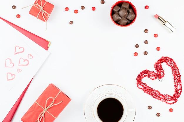Koffiekopje, snoepjes, lippenstift, hartvorm en geschenkdoos op witte achtergrond. valentijnsdag concept frame. Premium Foto