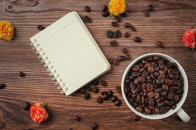 Koffiekopjes en koffiebonen op tafel, internationale dag van koffie concept. Gratis Foto