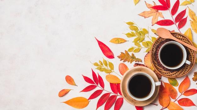 Koffiekoppen en kleurrijke herfstbladeren kopiëren ruimte Gratis Foto