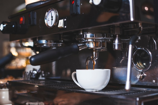 Koffiemachine giet vers koffie in witte kop Gratis Foto