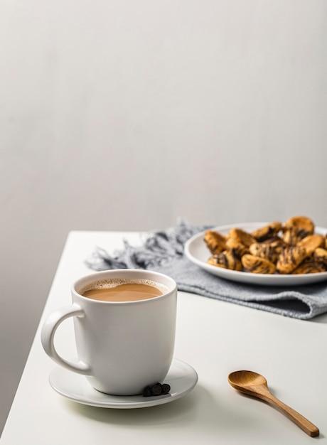 Koffiemok op tafel met plaat van koekjes Gratis Foto