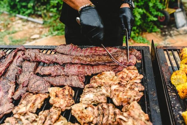Kok die geroosterd vlees voorbereiden tijdens een barbecue. Premium Foto