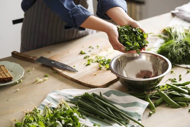 Koken. chef-kok snijdt greens in de keuken Gratis Foto