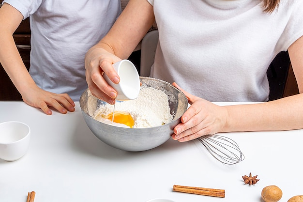 Koken chocoladekoekjes of peperkoek voor kerstmis en nieuwjaar. traditioneel feestelijk bakken, bakken met kinderen. stap 5 giet melk in de kom. stap voor stap recept. Premium Foto