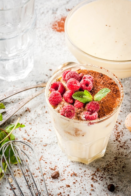 Koken italiaans eten dessert tiramisu, met alle benodigde ingrediënten cacao, koffie, mascarpone kaas, munt en frambozen Premium Foto