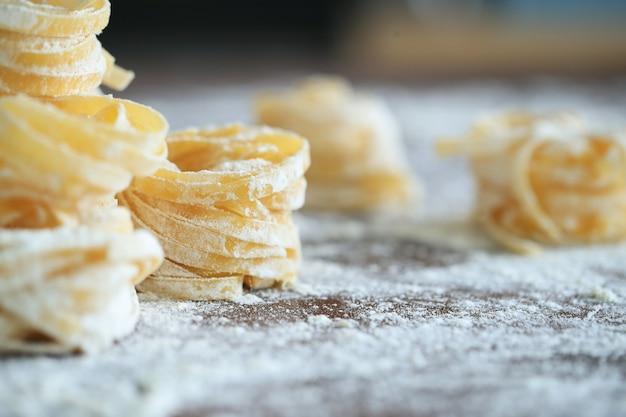 Koken italiaanse zelfgemaakte pasta op donkere achtergrond Gratis Foto