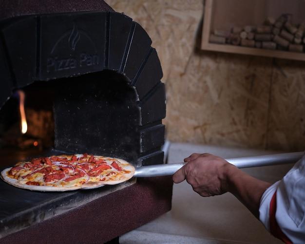 Koken nemen pizza uit klei-oven met vlammen Premium Foto