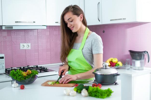 Kokende vrouw die rijpe groenten voor gezonde verse salades en schotels in keuken thuis hakken. koken voorbereiding voor het avondeten Premium Foto