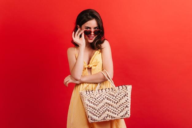 Koket meisje in zomeroutfit glimlacht lief terwijl ze haar stijlvolle zonnebril afdoet. portret van een jonge vrouw met donker krullend haar op rode muur. Gratis Foto