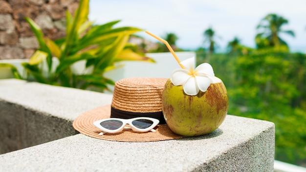Kokos cocktail cocktail versierd plumeria, stro hoed en zonnebril op tafel. Gratis Foto