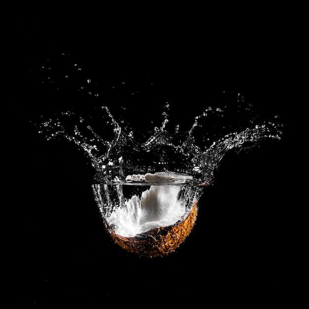 Kokosnoot die zich in het water stort Gratis Foto