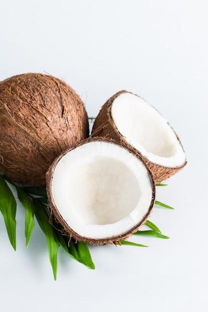 Kokosnoot met groene bladeren op een witte achtergrond. Premium Foto