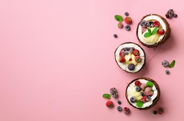 Kokosnootijs met verse bessen in kokosnotenhelften. eten in een minimale platte lay-stijl. Premium Foto