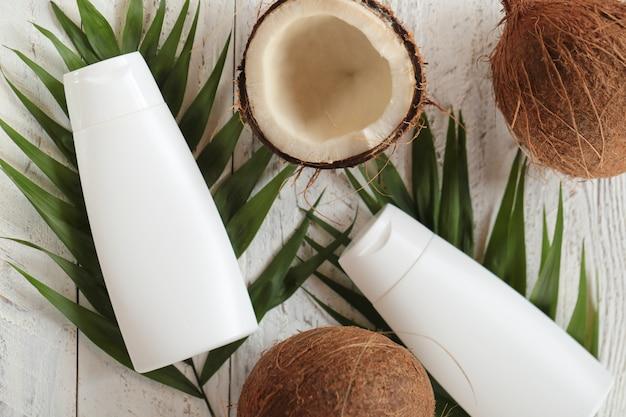 Kokosolie. zuivere natuurlijke kokosolie in witte flessen en verse kokosnoot in een snee met palmblad Premium Foto
