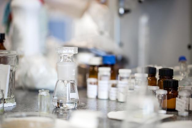 Kolven met vloeistoffen in een laboratorium, een fabriek van de farmaceutische industrie en een productielaboratorium, chemieconcept Premium Foto