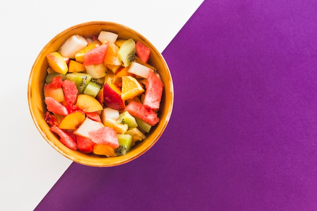 Kom fruitsalade op witte en purpere achtergrond Gratis Foto