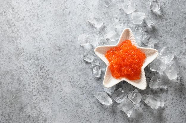 Kom in vorm van ster met rode kaviaar op ijs op grijze steenlijst. uitzicht van boven. ruimte voor tekst. Premium Foto