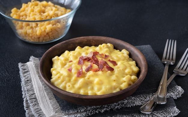 Kom macaroni en kaas met plakjes gebakken spek Premium Foto