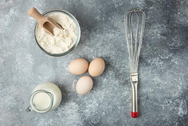 Kom meel, eieren en snorhaar op marmeren oppervlak. Gratis Foto