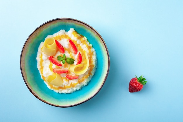 Kom melkrijstpap met aardbeien, mango's Premium Foto